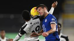 Bek Chelsea, Cesar Azpilicueta (kanan) berduel udara dengan striker Fulham, Ademola Lookman dalam laga lanjutan Liga Inggris 2020/21 pekan ke-18 di Craven Cottage, Sabtu (16/1/2021). Chelsea menang 1-0 atas Fulham. (AFP/Mike Hewitt/Pool)