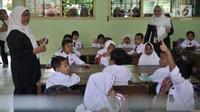 Dua guru mendampingi murid yang mengikuti aktivitas belajar mengajar di SDN Jatinegara Kaum 15 Pagi, Jakarta, Senin (15/7/2019). Sebanyak 32 anak menjadi murid baru SDN tersebut pada hari pertama masuk sekolah tahun ajaran 2019/2020. (merdeka.com/Iqbal S Nugroho)