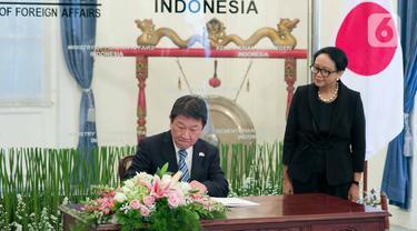 Menteri Luar Negeri Retno Marsudi (kanan) menyaksikan Menteri Luar Negeri Jepang Motegi Toshimitsu menandatangani buku tamu saat tiba di Gedung Kemlu, Jumat (10/1/2020). Kunjungan membahas kerjasama di bidang investasi termasuk pengembangan pulau terluar seperti Natuna. (Liputan6.com/Faizal Fanani)