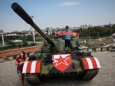 Suporter Red Star Belgrade berpose di tank T-55 yang terparkir di tribun utara Stadion Rajko Mitic, Belgrade, Serbia, Selasa (27/8/2019). Kehadiran tank tersebut memicu protes dari pihak Kroasia yang sempat berperang merebut kemerdekaannya dari Yugoslavia. (OLIVER BUNIC/AFP)