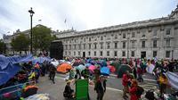 Para aktivis iklim duduk dalam tenda saat mereka berkemah di Westminster, London, Inggris, Selasa (8/10/2019). Pemberontakan Kepunahan adalah bagian dari upaya para aktivis dalam mendorong para pemimpin global untuk serius merespons perubahan iklim. (Ben STANSALL/AFP)