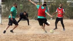 Seorang pemain menembak bola saat bermain di lapangan tanah sebelum buka puasa selama bulan Ramadhan, di ibu kota Libya, Tripoli (24/4/2021). (AFP/Mahmud Turkia)