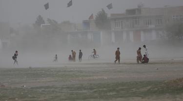 Anak laki-laki Afghanistan bermain saat badai pasir di pinggiran Kabul, Afghanistan (25/8/2020). Sebuah badai pasir hebat melanda Kabul. Badai menyebabkan jarak pandang jadi berkurang. (AP Photo / Rahmat Gul)