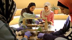 Anak-anak Palestina meletakkan tanaman ke dalam botol plastik di Pusat Anak-Anak Al-Qattan, Gaza City, Senin (20/7/2020). Anak-anak Palestina belajar bagaimana memanfaatkan kembali botol dan wadah plastik bekas untuk dekorasi taman. (Xinhua/Rizek Abdeljawad)