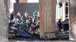 Petugas saat memadamkan kebakaran di paviliun utama situs Festival Film El Gouna yang hangus terbakar di pantai Laut Merah Mesir (12/10/2021). Kobaran api melalap aula utama festival, hanya sehari sebelum acara dimulai, seperti dilansir ArabNews. (AFP)