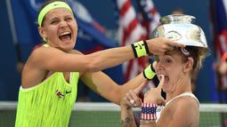 Bethanie Mattek-Sands (kanan) dan Lucie Safarova merayakan kemenangan usai menjuarai Ganda Putri AS Terbuka 2016 di USTA Billie Jean King National Tennis Center, New York, (11/9/2016). (AFP/ Timothy A. Clary)