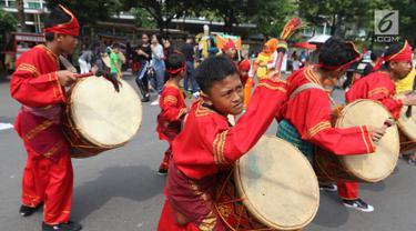 Seniman cilik memainkan alat musik tambur khas Minangkabau saat car free day (CFD) di Jakarta, Minggu (13/1). Pertunjukan tersebut untuk mengenalkan alat musik tradisional Nusantara kepada masyarakat. (Liputan6.com/Angga Yuniar)