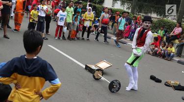 Seniman pantomim tampil menghibur pengunjung car free day di Jakarta, Minggu (1/7). Aksi tersebut dilakukan guna mengumpulkan biaya yang akan digunakan untuk menikah. (Liputan6.com/Immanuel Antonius)