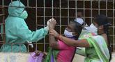 Seorang wanita (tengah) bereaksi ketika petugas kesehatan mencoba mengumpulkan sampel usapnya untuk menguji virus corona Covid-19 di daerah kumuh di Hyderabad (23/9/2020). (AFP/Noah Seelam)