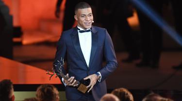 Striker Paris Saint-Germain, Kylian Mbappe setelah menerima penghargaan Trophee Kopa pada seremoni Ballon d'Or 2018 di Grand Palais, Senin (3/12). Ini merupakan penghargaan bagi pesepakbola terbaik yang masih berusia di bawah 21 tahun. (FRANCK FIFE/AFP)