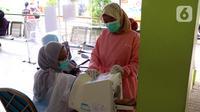 Tenaga kesehatan menjalani pemeriksaan sebelum menjalani vaksinasi COVID-19 di Puskesmas Jurang Mangu, Tangerang Selatan, Jumat (15/1/2021). Program vaksinasi COVID-19 tahap pertama kepada tenaga kesehatan mulai dilakukan di berbagai daerah di Indonesia. (Liputan6.com/Angga Yuniar)