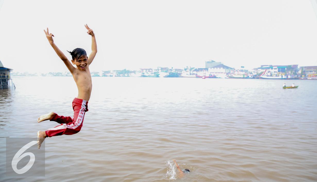 Seorang anak melompat untuk berenang di Sungai Kapuas, Pontianak, Kalimantan Barat, Sabtu (22/8/2015). Anak-anak yang tinggal sekitar Sungai Kapuas biasa mandi dan berenang di aliran tersebut setiap pagi dan sore hari. (Liputan6.com/Faizal Fanani)