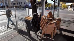 Kursi kafe ditumpuk di kawasan Lygon Street di Melbourne, Rabu (2/6/2021). Pelaksana tugas Menteri Utama Victoria James Merlino mengumumkan lockdown akan diperpanjang tujuh hari lagi, setelah ada enam kasus baru menjadikan total 60 kasus positif hingga hari Rabu (2/6). (William WEST / AFP)