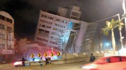 Kondisi sebuah bangunan yang miring setelah pondasinya ambruk usai terjadi gempa di Hualien, Taiwan (7/2). Sebuah bangunan ambruk dan jalan raya di dekatnya terpaksa ditutup. (Biro Pemadam Kebakaran Hualien via AP)