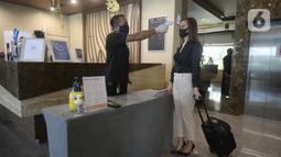 Petugas mengecek suhu tubuh pengunjung yang akan menginap di Hotel Grand Whiz Poins Simatupang, Jakarta, Kamis (16/4/2020). Hotel ini menyediakan paket isolasi mandiri untuk mendukung program pembatasan sosial berskala besar (PSBB) di tengah pandemi virus corona COVID-19. (merdeka.com/Dwi Narwoko)