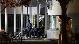 Petugas mengecek kantor polisi setelah ledakan dahsyat di pintu masuk utama di Helsingborg, Swedia (18/10). Tidak ada korban dalam ledakan yang terjadi di kantor polisi tersebut. (AFP Photo/TT News Agency /Johan Nilsson/Sweden Out)