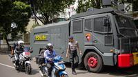 Pengendara sepeda motor melintasi mobil water cannon yang disiagakan di Kantor Komisi Pemilihan Umum (KPU), Jakarta, Kamis (18/4). Hal tersebut dilakukan untuk mengantisipasi ancaman keamanan usai Pemilu 2019. (Liputan6.com/Faizal Fanani)