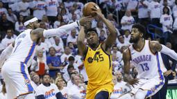 Pebasket Utah Jazz, Donovan Mitchell, berusaha melewati pebasket Oklahoma City Thunder, Carmelo Anthony, pada gim kedua play-off NBA Wilayah Barat, Rabu (18/4/2018). Jazz menang 102-95 atas Thunder. (AP/Sue Ogrocki)