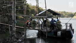 Pengendara sepeda motor membawa pakan ternak saat menyeberangi Sungai Brantas menaiki perahu eretan di Desa Mayan, Mojo, Kediri, Sabtu (29/9). Meski sudah ada jembatan, warga memilih perahu eretan sebagai penunjang aktivitas. (Merdeka.com/Iqbal Nugroho)
