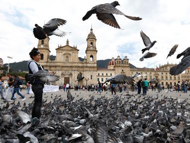Kawanan burung merpati memenuhi Alun-Alun Bolivar di Bogota, Kolombia, 2 Oktober 2018. Pemerintah Bogota berusaha mengurangi jumlah populasi merpati melalui larangan bagi pengunjung untuk tidak memberi makan lagi burung-burung itu. (AP/Fernando Vergara)