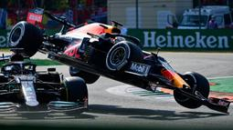 Alih-alih berhasil melewati Hamilton, mobil Verstappen malah bertabrakan hingga terangkat dan mendarat di atas rivalnya tersebut. Bahkan, sisi dalam ban mobil Verstappen mengenai helm Hamilton yang cukup beruntung terlindungi piranti halo. (Foto: AFP/Andrej Isakovic)