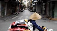 Seorang penjual berjalan melewati jalan sepi di tengah kekhawatiran tentang penyebaran Virus Corona COVID-19 di Hanoi Vietnam pada 26 Maret 2020. (Nhac Nguyen / AFP)