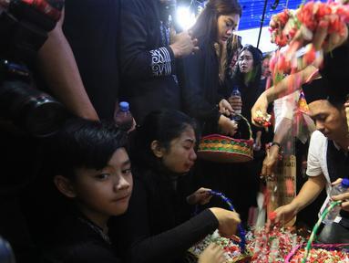 Sejumlah keluarga dan kerabat menaburkan bunga  di atas makam Julia Perez di Taman Pemakaman Umum Pondok Ranggon, Cijantung, Jakarta Timur, Sabtu (10/6). Jupe menghembuskan napas terakhir di RSCM, pada Sabtu 10 Juni 2017. (Liputan6.com/Herman Zakharia)