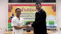 Salah seorang remaja, Adul Samon menerima kartu identitas sebagai warga negara Thailand di distrik Mae Sai, Rabu (8/8). Korban gua Thailand tersebut selama ini hidup tanpa memiliki status kewarganegaraan. (Chiang Rai Public Relations Office via AP)