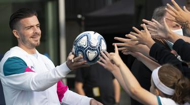 Pemain baru Manchester City, Jack Grealish, memberikan bola kepada para penngemar saat diperkenalkan di Stadion Etihad, Senin (9/8/2021). Manchester City memecahkan ekor transfer Inggris dengan mendatangkan Jack Grealish dari Aston Villa dengan harga £100 juta ($139 juta). (AP Photo/Jon Super)