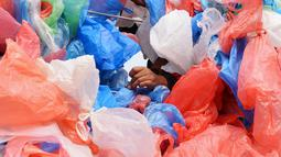 Relawan Nepal mengikat kantong plastik daur ulang membentuk replika Laut Mati di Kathmandu pada 5 Desember 2018. Kegiatan ini diharap dapat meningkatkan kesadaran masyarakat akan banyaknya sampah plastik yang mencemari lautan dunia (PRAKASH MATHEMA / AFP)