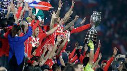 Para pemain Chili bersorak mengangkat trofi usai mengalahkan Argentina saat Final Copa America 2015 di Stadion Nasional, Santiago, Chili, (4/7/2015). Chili menang lewat adu penalti atas Argentina dengan skor 4-1. (REUTERS/Jorge Adorno)