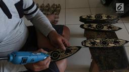 Pengrajin tengah membuat sovenir papan seluncur di Bali, Senin (15/10). Sektor pariwisata menjadi salah satu penyumbang cepat datangnya devisa. (Liputan6.com/Angga Yuniar)