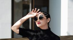 Menggunakan busana berwarna hitam dilengkapi aksesoris kacamata berlensa gelap membuat penampilan aktris sekaligus model ini semakin stunning. Kacamata dengan lensa besar membuat wajahnya terlihat lebih tirus. (Liputan6.com/IG/@ririnekawati/)