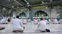 "Warga Saudi dan ekspatriat melakukan sholat ""Al Fajr"" di Masjidil Haram di kota suci Mekkah (18/10/2020). Salat di Masjidil Haram ini dilaksanakan dengan menerapkan protokol kesehatan ketat untuk mengantisipasi penularan virus, seperti pemakaian masker dan menjaga jarak fisik. (AFP/STR)"