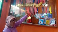 Siti Aisah, ibunda lifter Windy Cantika Aisah, memamerkan medali prestasi putrinya. (Bola.com/Erwin Snaz)