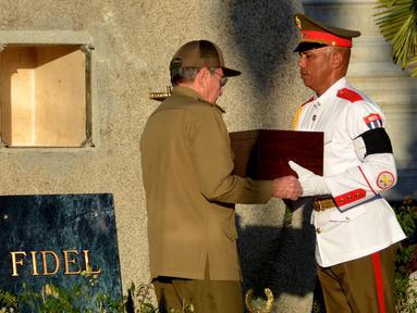 Presiden Kuba, Raul Castro (kiri) menerima kotak kayu berisi abu mantan Presiden Kuba, Fidel Castro saat akan dimakamkan di peristirahatan terakhir di Santa Ifigenia Cemetery, di Santiago, Kuba (4/12). (REUTERS/ACN/Marcelino Vazquez)