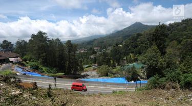Kendaraan melintasi di sekitar area yang longsor di kawasan Ciloto, Cianjur, Jawa Barat, Sabtu (31/3). Longsor yang terjadi pada Rabu (28/3) lalu diduga adanya pergerakan tanah sehingga menyebabkan longsor. (Liputan6.com/Helmi Fithriansyah)