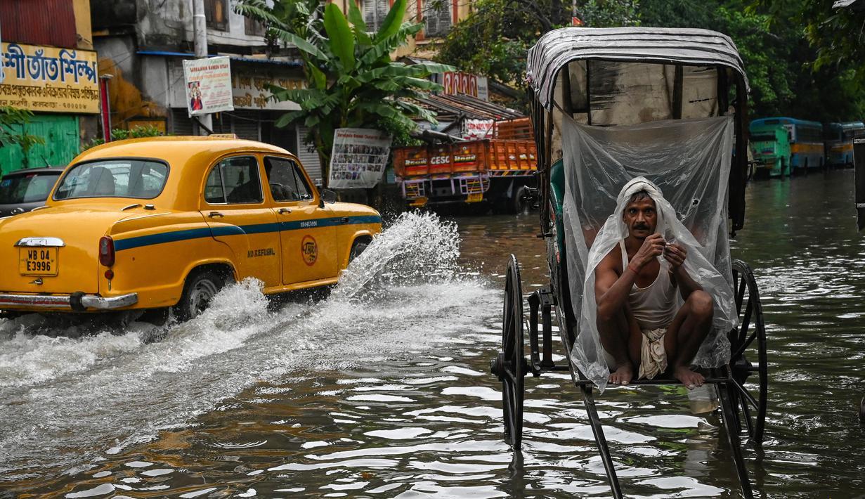 Seorang penarik becak membungkus dirinya dengan lembaran plastik sambil menunggu untuk mengangkut pelanggan melintasi jalan yang tergenang air setelah hujan lebat di Kolkata (20/9/2021). Hujan dilaporkan dipicu oleh sirkulasi siklon yang terbentuk di atas Teluk Benggala. (AFP/Dibyangshu Sarkar)