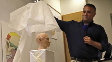 Liran Carmel dari Universitas Hebrew menunjukkan model cetak 3D wajah gadis spesies manusia prasejarah Denisovan setelah penelitian menggunakan data metilasi DNA selama konferensi pers di Universitas Ibrani di Yerusalem (19/9/2019). (AFP Photo/Menahem Kahana)