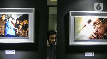 Pengunjung mengintip dari celah-celah pada pameran Satu Dekade Haul Presiden ke IV Republik Indonesia KH Abdurrahman Wahid atau Gus Dur di Kantor DPP PKB, Jakarta, Rabu (15/1/2020). Pameran sekaligus lomba foto ini diikuti oleh puluhan fotografer dari seluruh Indonesia. (Liputan6.com/Faizal Fanani)