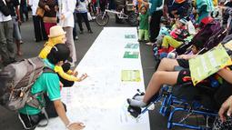 Masyarakat membubuhkan tanda tangan pada Peringatan Hari Cerebral Palsy Sedunia di area Car Free Day, Bundaran HI, Jakarta, Minggu (8/10). Kegiatan tersebut untuk menggalang kepedulian bagi penyandang Cerebral Palsy. (Liputan6.com/Angga Yuniar)