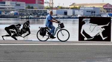 Pengendara sepeda melintas di samping patung erotis karya seniman Antoni Miro yang dipamerkan di pelabuhan Valencia, Spanyol (19/9). (AFP Photo/Jose Jordan)