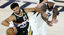 Pemain Denver Nuggets, Jamal Murray, berebut bola dengan pemain Utah Jazz, Royce O'Neale, pada ronde pertama playoff NBA musim 2020 di The Field House, Florida, Selasa (18/8/2020). Denver Nuggets menang 135-125 atas Utah Jazz. (AFP/Ashley Landis/Pool/Getty Images)