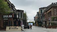 Penjaga toko  mengenakan pakaian pelindung menunggu pelanggan di sebuah jalan ritel di Wuhan di provinsi Hubei, China tengah (30/3/2020). Penjaga toko menyiapkan pembersih tangan dan memeriksa tanda-tanda demam pada pelanggan yang datang. (AP Photo/Olivia Zhang)