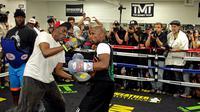 Roger Mayweather saat masih menangani Floyd Mayweather Jr dalam mempersiapkan diri menggadapi pertandingan. (JOHN GURZINSKI / AFP)