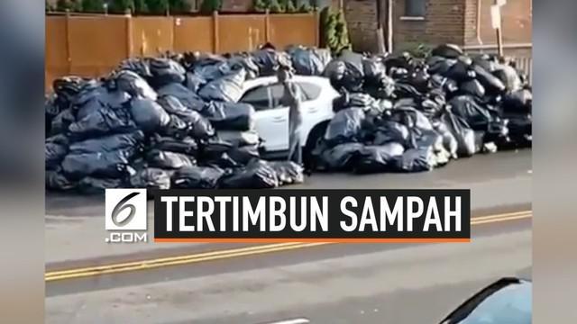 Lantaran parkir sembarangan, sebuah mobil tertimbun kantong sampah. Mobil tersebut terparkir selama semalaman di zona pemuatan sampah sebuah gedung apartemen di New York.