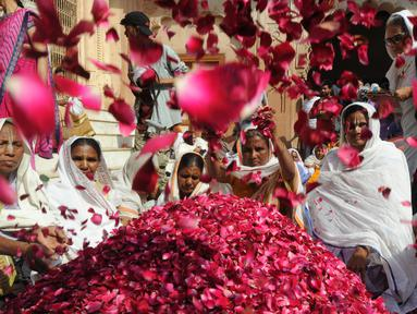 Para janda India melemparkan kelopak bunga saat menghadiri festival holi di kota Vrindavan, India, (9/3). Holi merupakan festival awal musim semi yang ditandai dengan aksi melempar bubuk berwarna-warni. (AFP Photo / Dominique Faget)