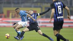 Striker Inter Milan, Mauro Icardi, berebut bola dengan pemain Napoli, Marques Allan, pada laga Serie A di Stadion San Siro, Rabu (26/12). Inter Milan menang 1-0 atas Napoli. (AP/Luca Bruno)