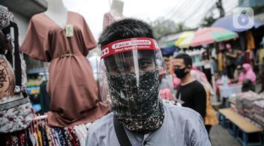 Pedagang menggunakan alat pelindung wajah (Face Shield) saat berjualan di Kawasan Tanah Abang, Jakarta, Senin (18/5/2020). Penggunaan alat pelindung wajah itu sebagai upaya untuk melindungi diri saat berhubungan dengan pembeli dalam pecegahan penyebaran COVID-19. (Liputan6.com/Faizal Fanani)