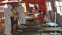 Petugas medis membawa pasien COVID-19 menuju tenda darurat di RSUD Bekasi, Rabu (23/6/2021). Tenda darurat didirikan sebagai upaya menambah ruang IGD yang dapat menampung 30 pasien menyusul ruangan di rumah sakit sudah penuh akibat lonjakan kasus Covid-19. (Liputan6.com/Herman Zakharia)